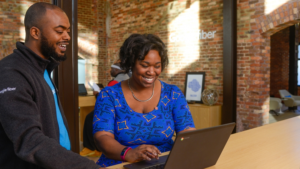 Alumna Tia Bethea chats with a coworker at the Google Fiber Space in downtown Raleigh.