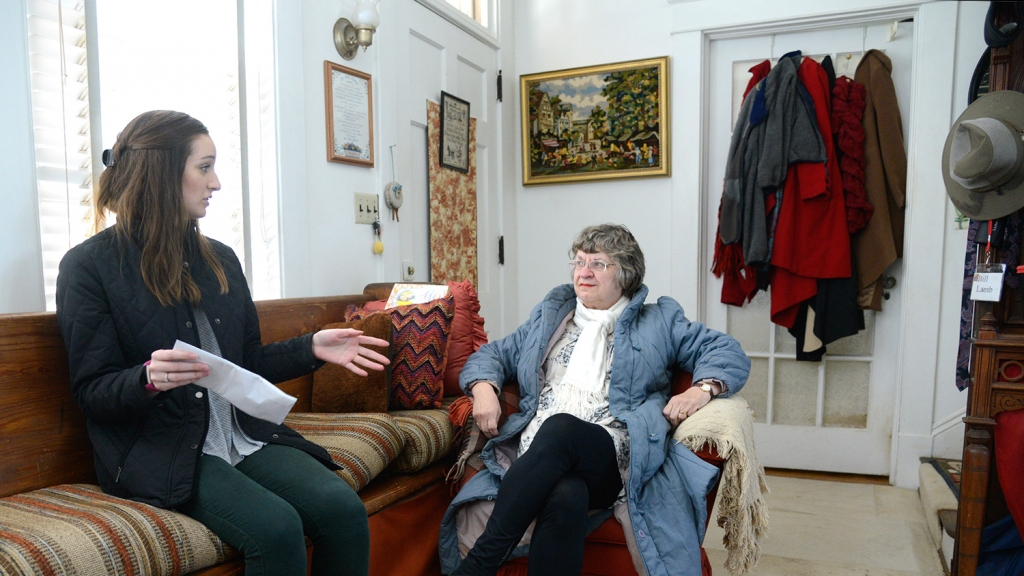 Social work student Bristol Bowman, left, discusses a neighborhood survey with Cameron Park resident Marty Lamb in Lamb's home near downtown Raleigh.