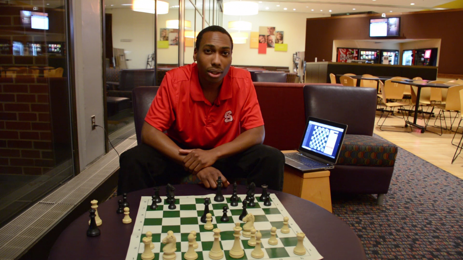 Justin Lockett sits at chess board