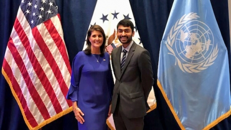 Standing in front of three flags, Amith Mandavilli poses with U.S. Ambassador Nikki Haley