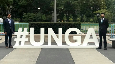 "Two men stand on both sides of a large sign reading, ""#UNGA"""