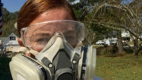 Brandy Osborne looks at the camera, wearing a Tyvek suit and a respirator mask.