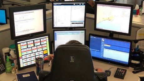 A 911 Center worker sits in front of several computer monitors.