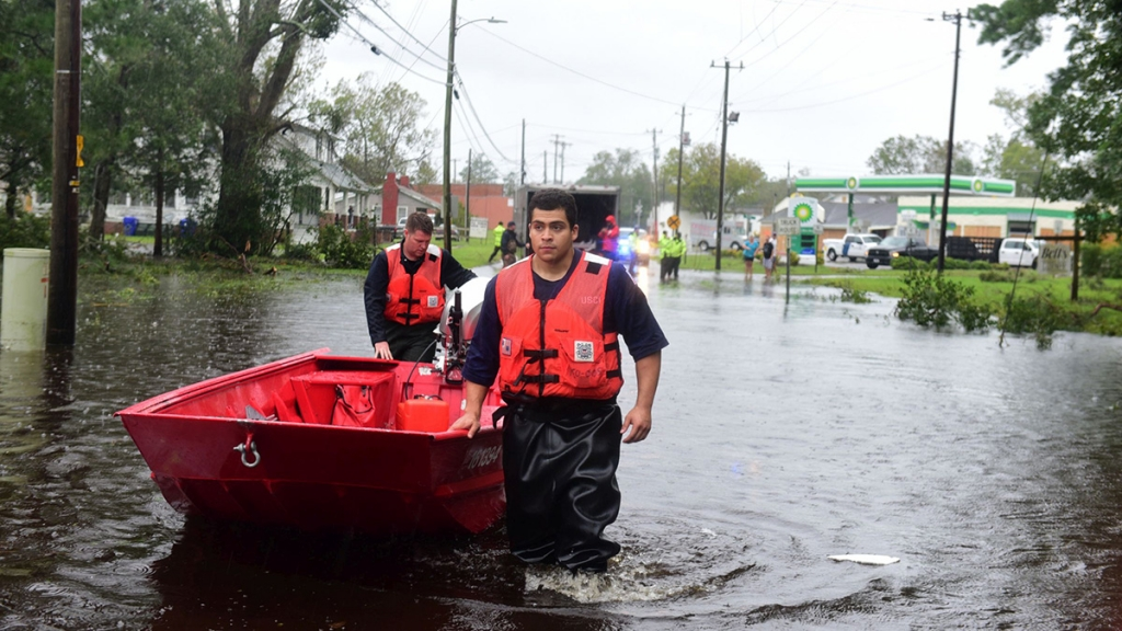 Coast Guard members wade through flood waters.