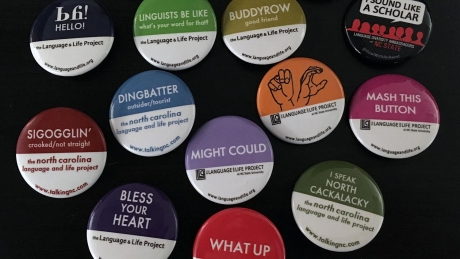 A collection of dialect buttons from the Language and Life Project sit on a black background.