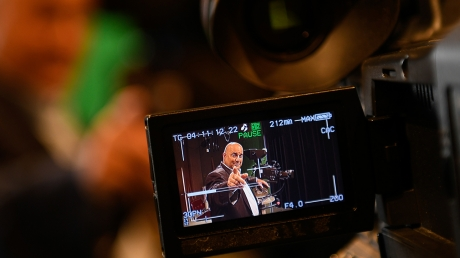Pictured through the lens of a video camera, John Ward wears a suit and points toward the camera.