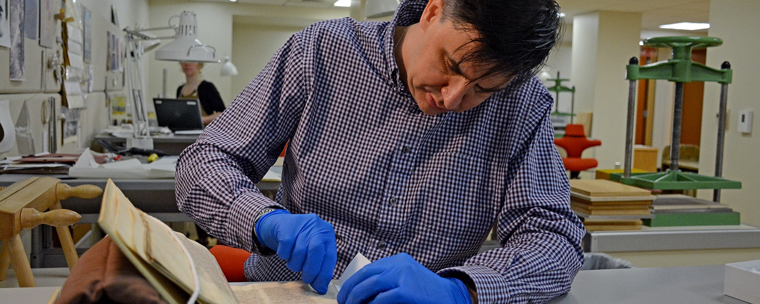 Wearing blue gloves, Tim Stinson rubs a plastic eraser against an old manuscript.