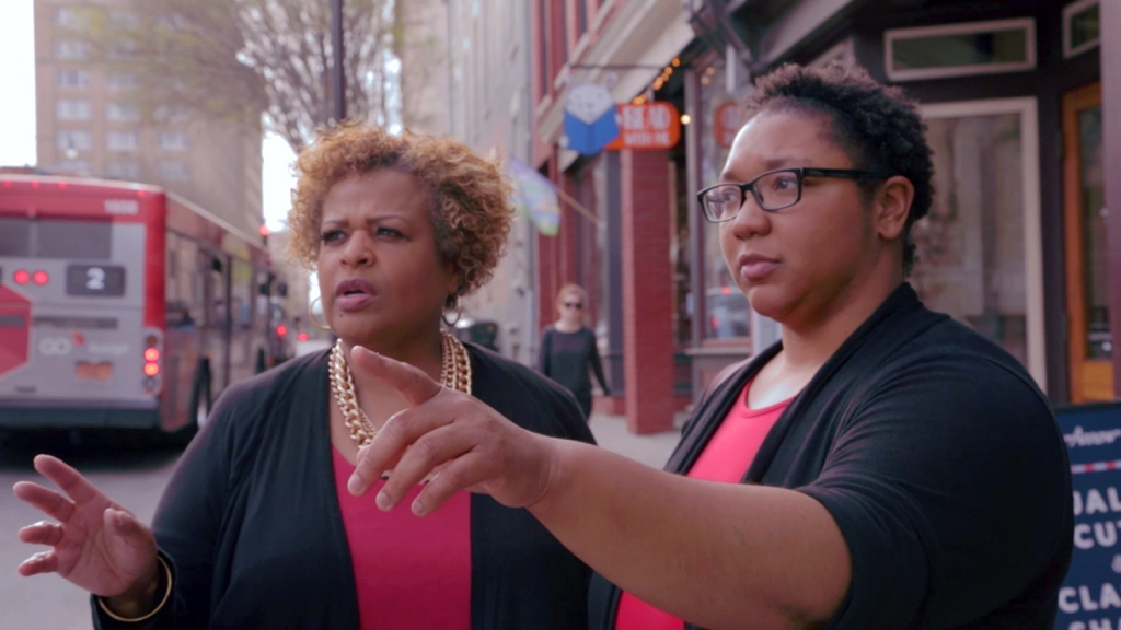 Lisa Withers and Sylvia West stand on Hargett Street in downtown Raleigh, pointing at a building.