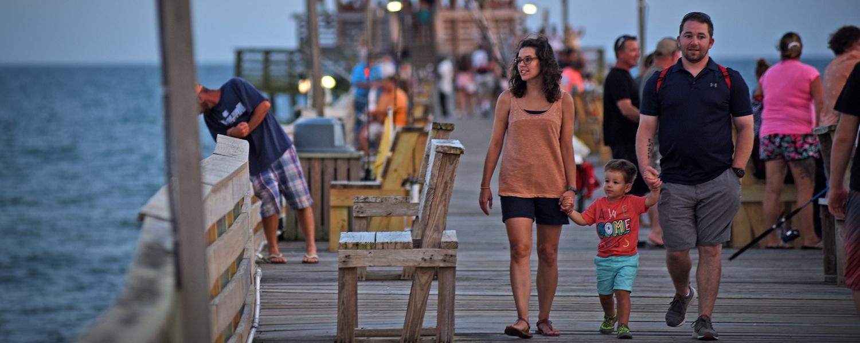 A family walks down a pier along the ocean.