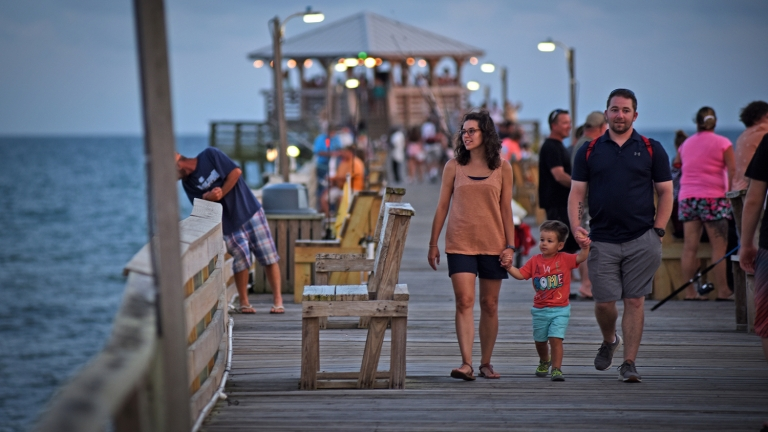 People walk down a fishing pier along the ocean.