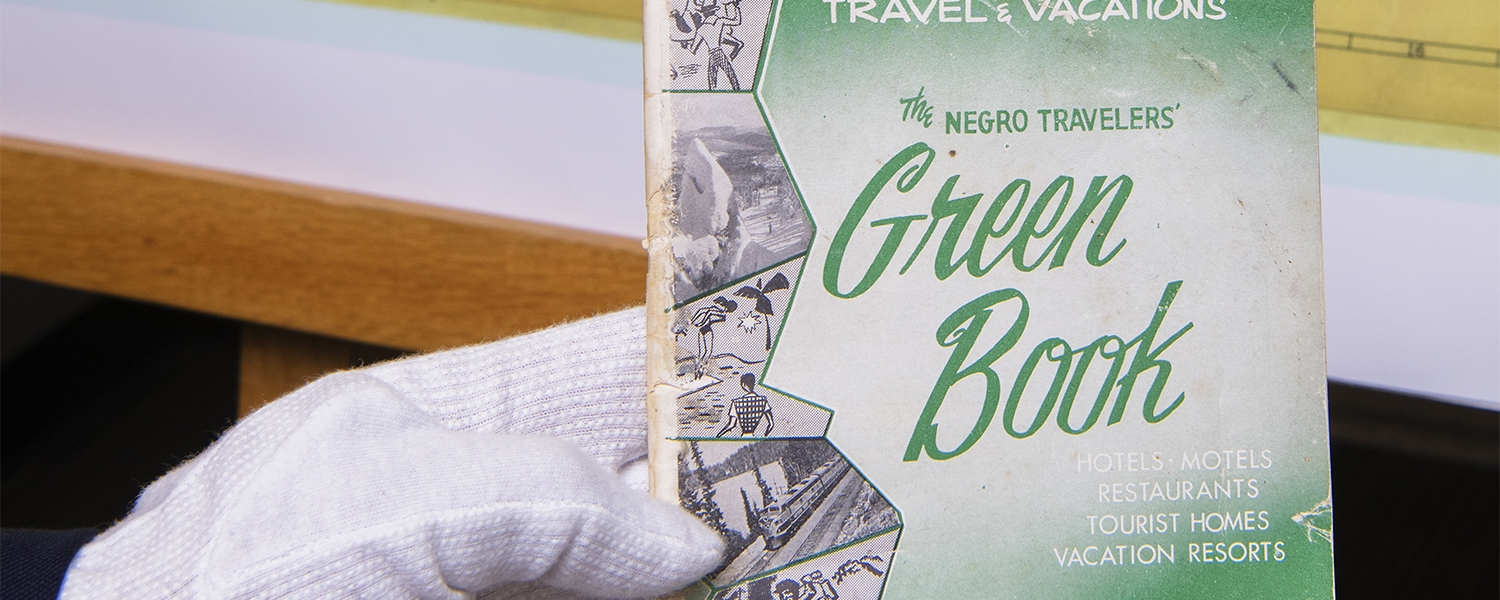 A gloved hand holds a copy of the Green Book