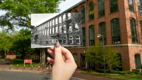 A hand holds up an archival photo of NC State's Tompkins Hall, in front of the Tompkins Hall of today.
