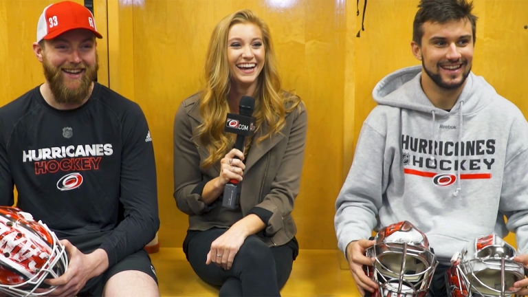 Holding a microphone. Abby Labar interviews two Carolina Hurricanes players