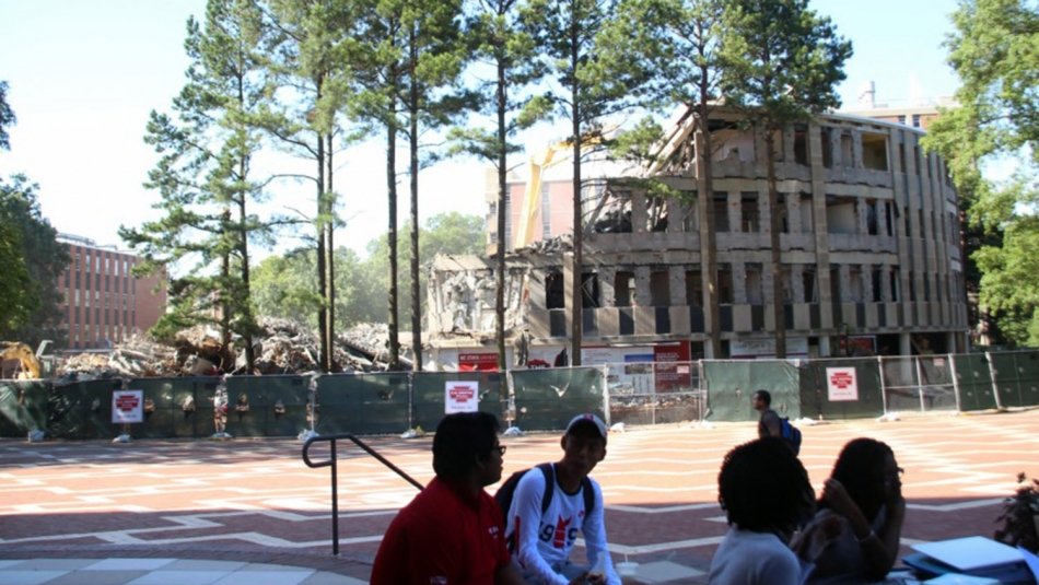 Students watch as Harrelson Hall is demolished