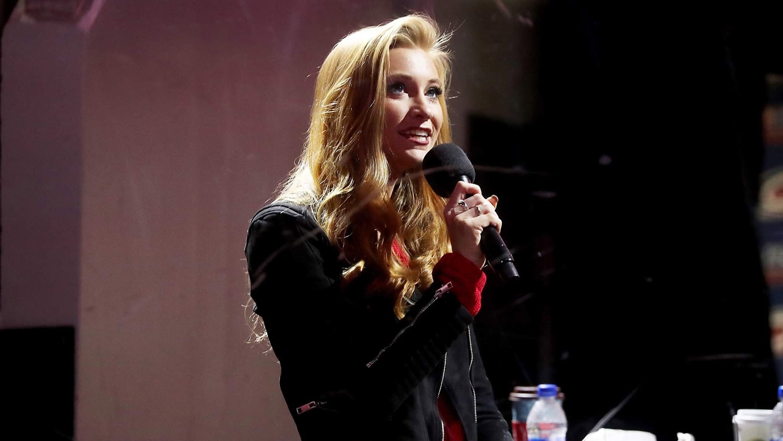 Alumna Abby Labar holding a microphone