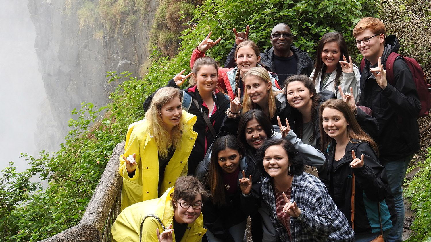 group stands in front of Victoria Falls