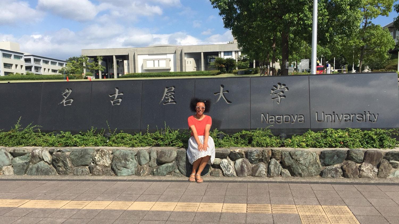 student sitting in front of Nagoya University sign