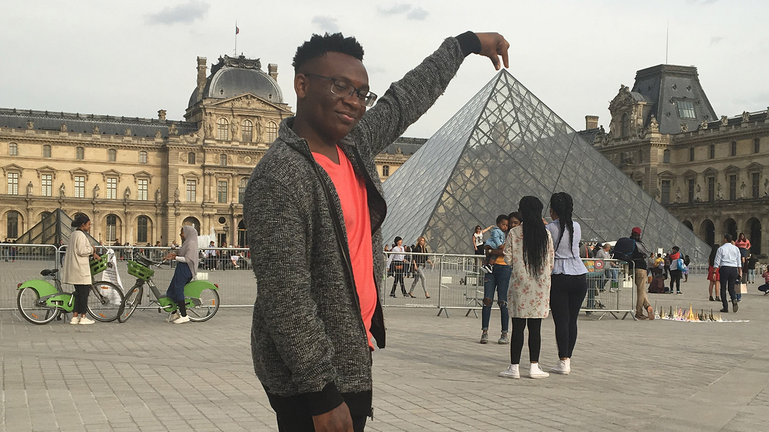 student standing in front of the Louvre