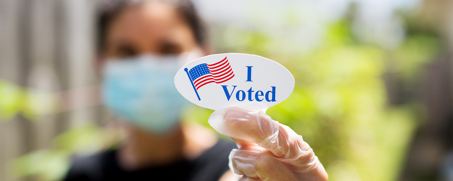 """A masked person holds up a sticker that reads, """"I voted."""""""