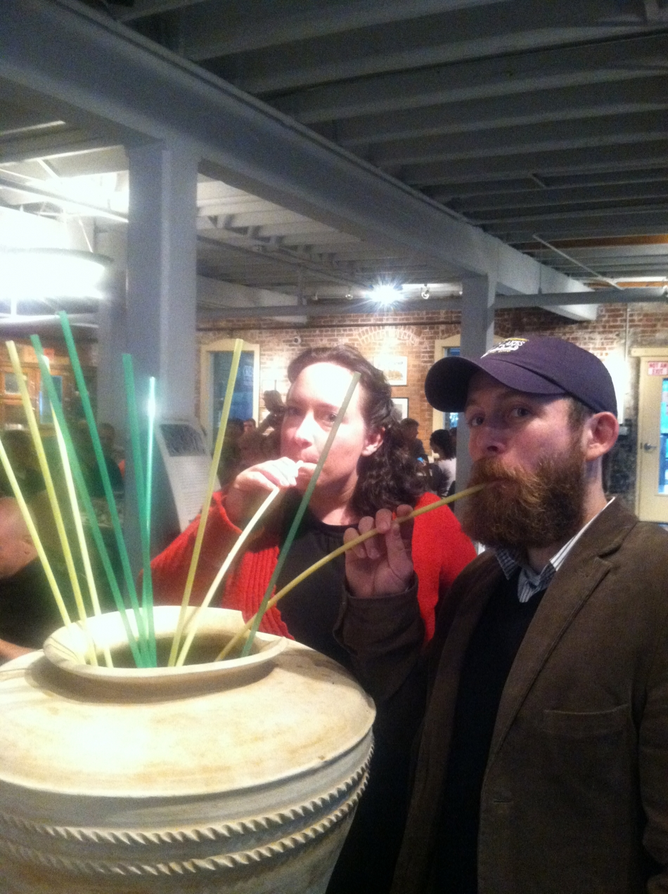 "man and woman sip an experimental beer ""Sumerian-style"" through long straws"