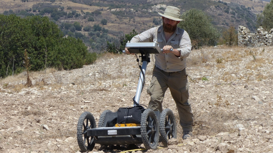 man conducts a ground-penetrating radar survey on the island of Cyprus