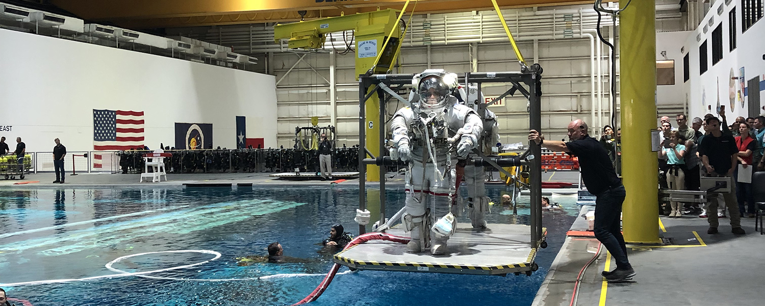Two astronaut candidates are raised from a buoyancy tank after training