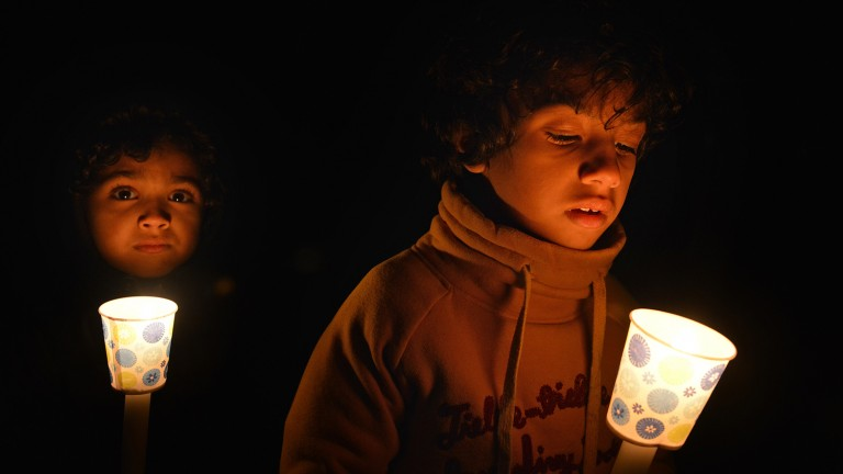 Two young boys holding candles at a vigil for Our Three Winners.