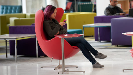 A student looks at her phone while sitting down at Hunt Library.