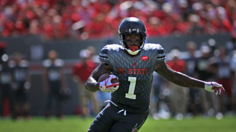 NC State athlete holds a football during a game.