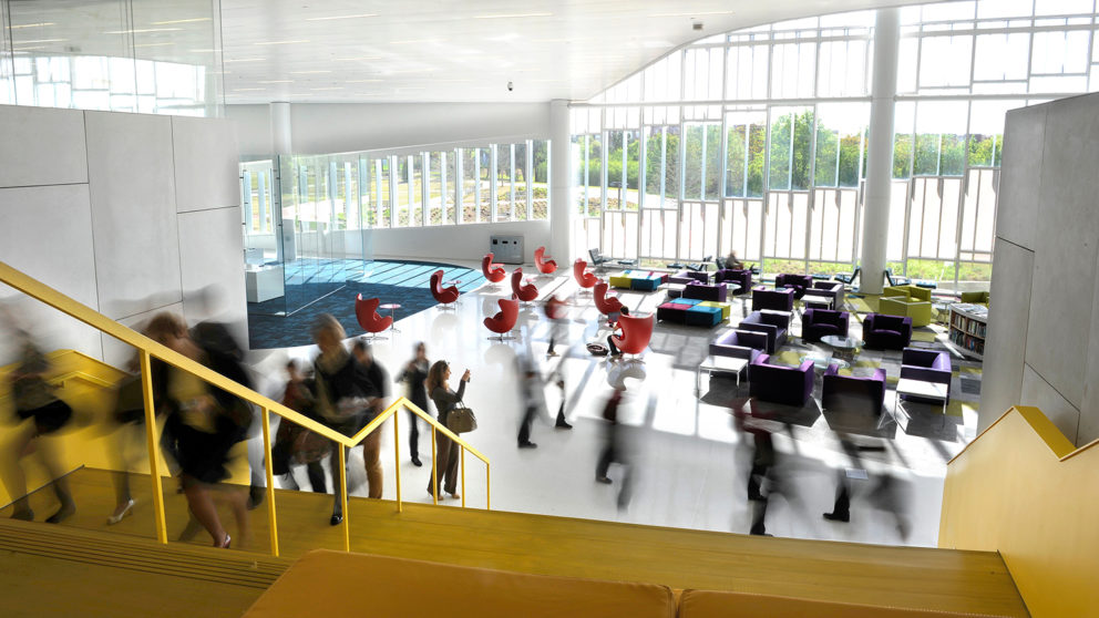 Students and faculty rush through the lobby of NC State's innovative Hunt Library