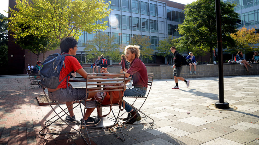Students chat at an outdoor table on NC State's campus.