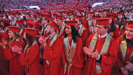 Students in red robes clap during their graduation ceremony on NC State's campus.