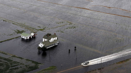 A pickup truck drives on a flooded road past a farmhouse that is surrounded by flooded fields from Tropical Storm Florence in Hyde County, N.C.