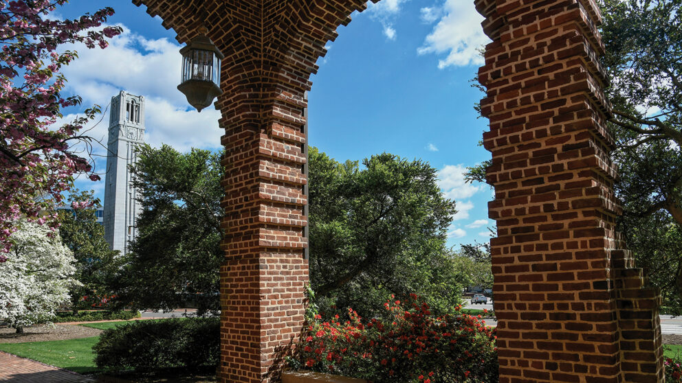 A brick archway outside of Holladay Hall, with the Belltower in the background.