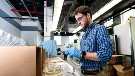 A man works to print face shields in NC State's 3D-printing lab.
