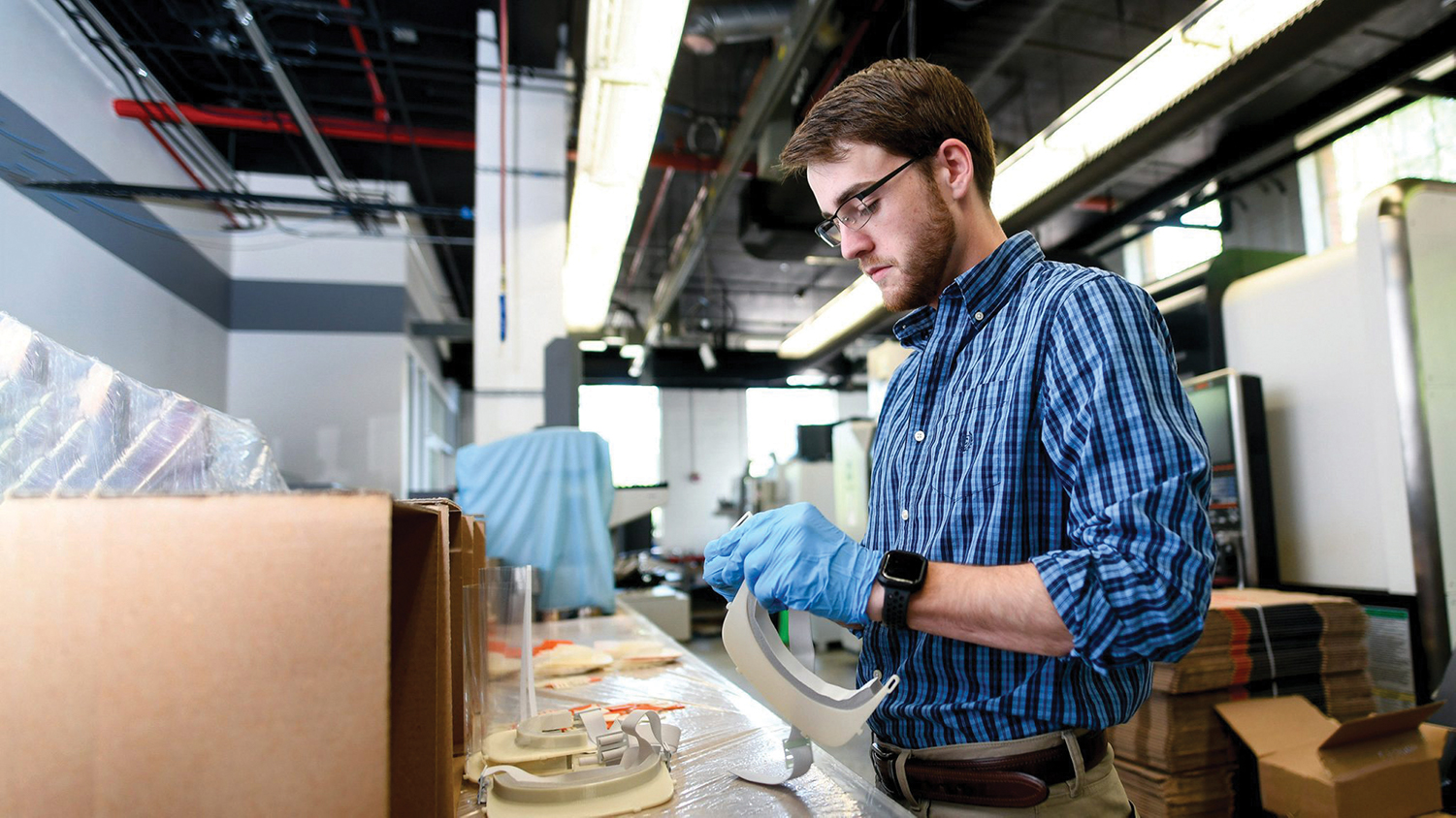 A man works to construct face shields in NC State's 3D-printing lab.