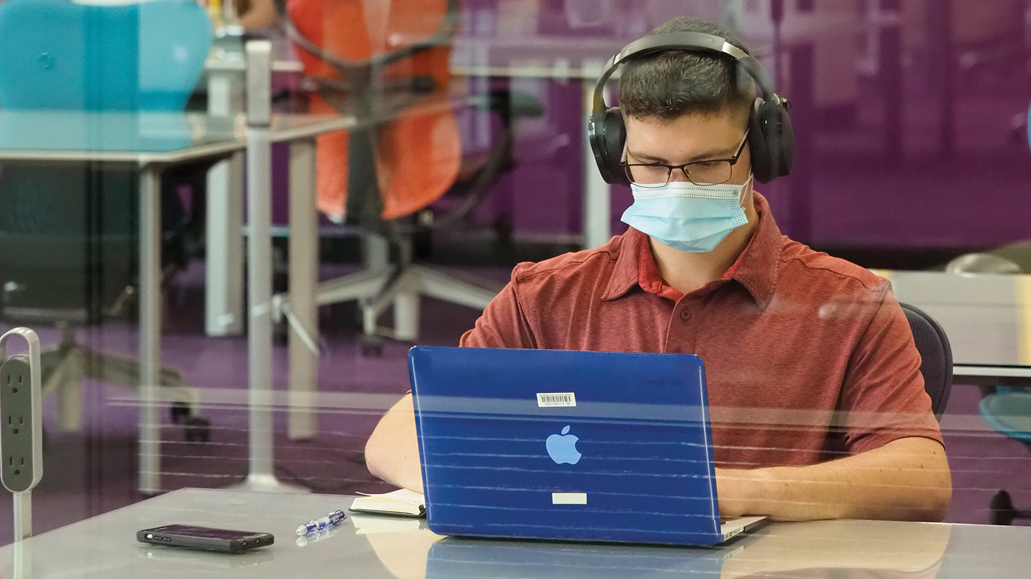 A student wearing a face mask studies in D.H. Hill Library.