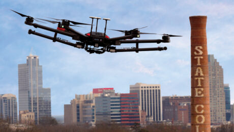 A drone flies above NC State's campus, with downtown Raleigh on the horizon.