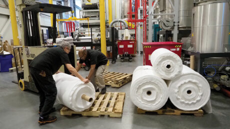 Two men in a warehouse handle rolls of innovative spunbond filtration material.