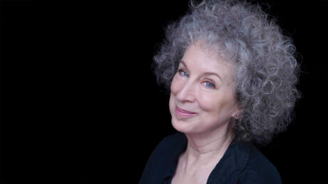 Author Margaret Atwood takes her headshot in front of a black backdrop.