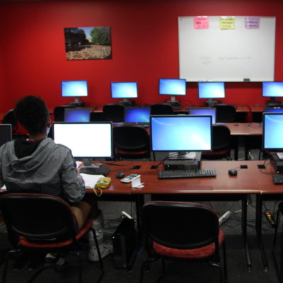 A lone student works on a computer in a computer lab