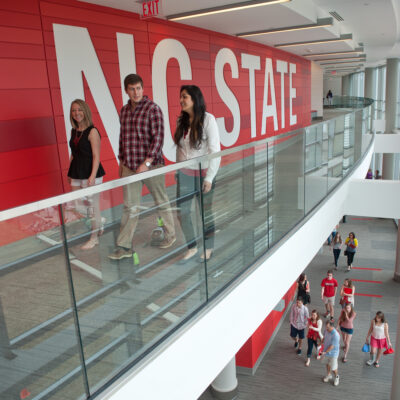 Students walk by the NC State logo in Talley Student Union