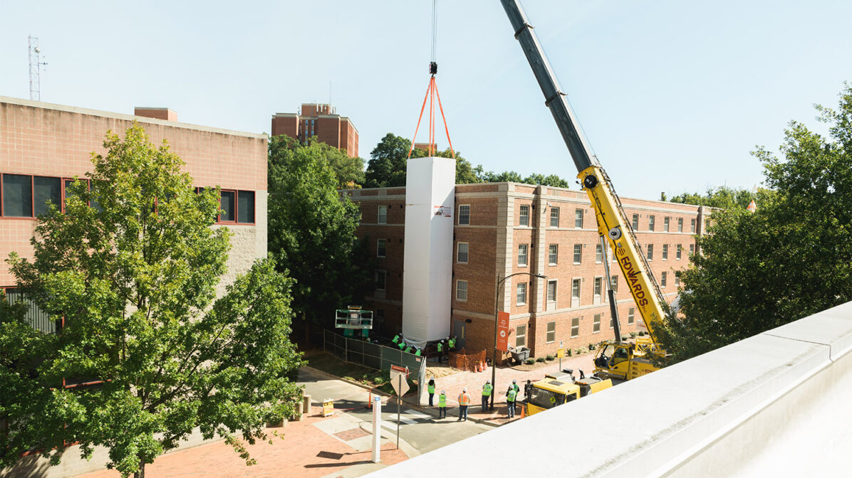 A construction crane places the new elevator shaft onto the side of Tucker Hall