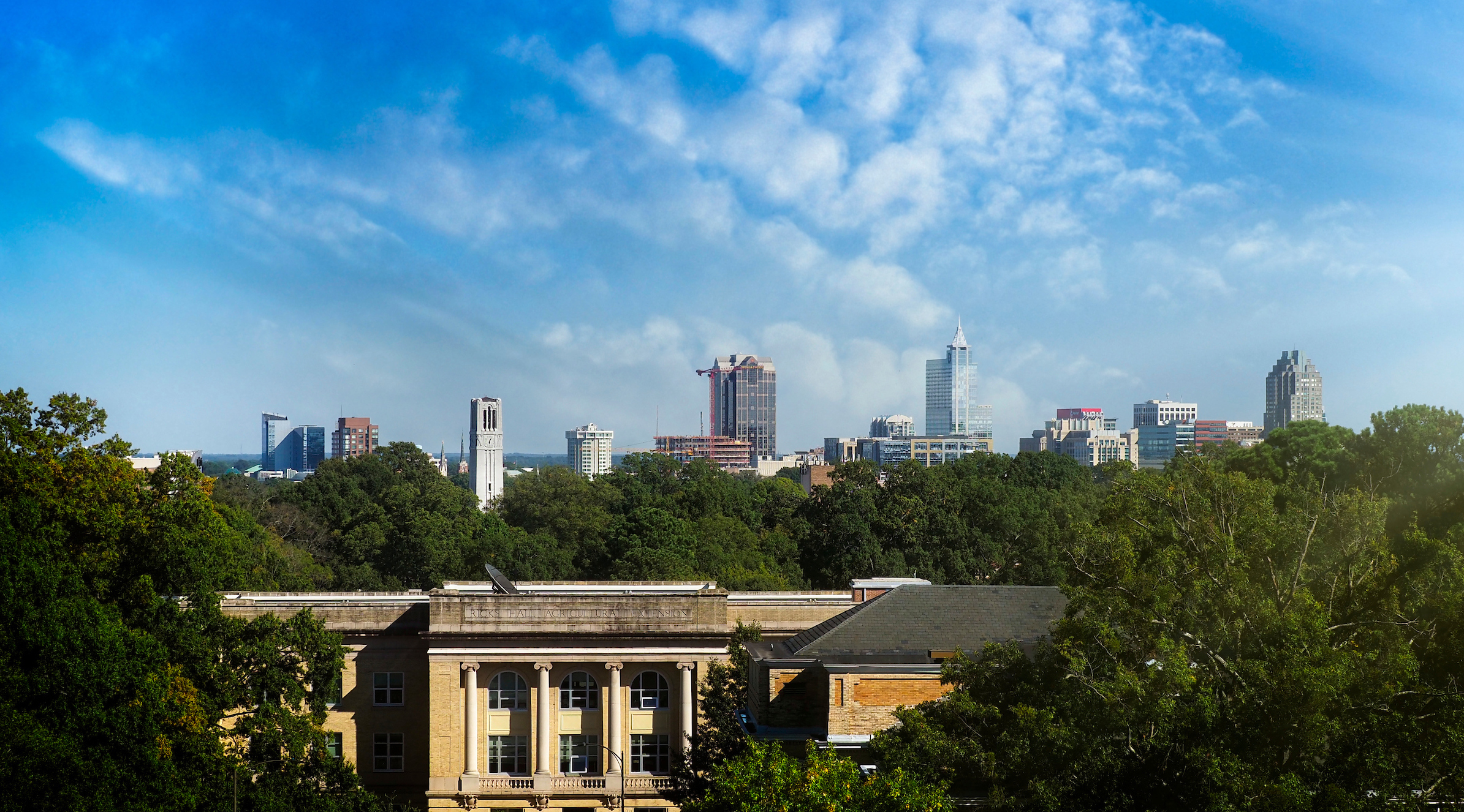 A skyline of Raleigh displays the NC State belltower and downtown high rise buildings