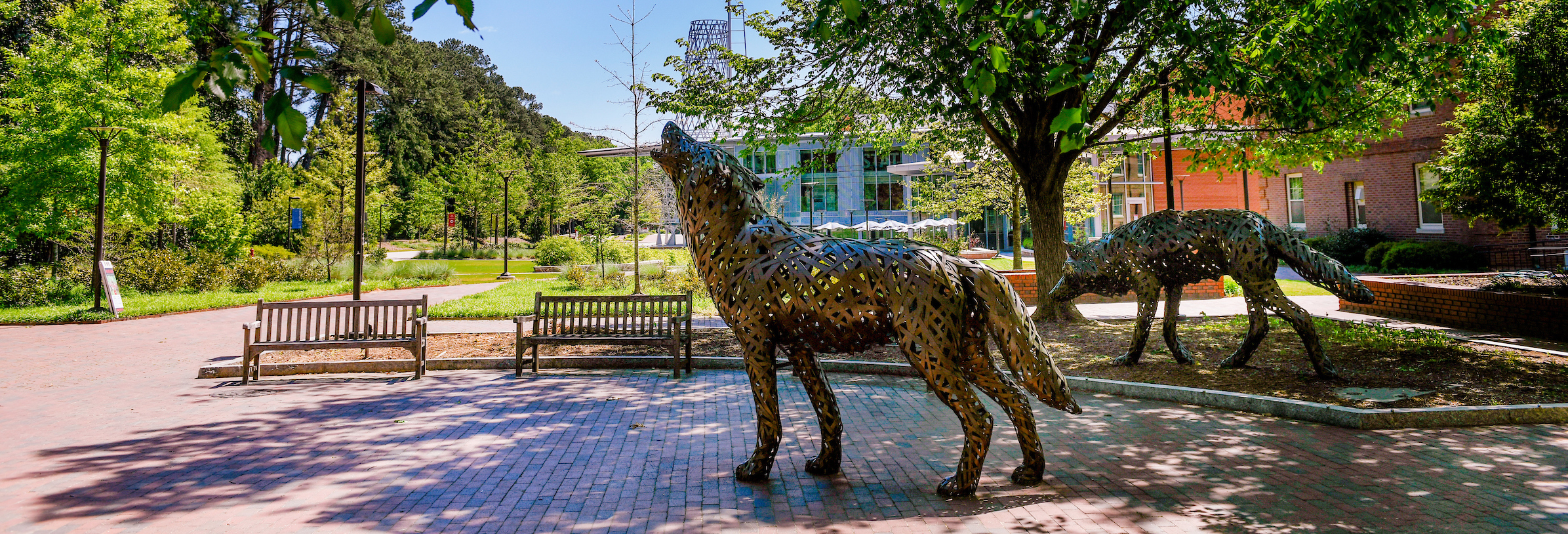 Copper wolves stand by the walkway to Stafford Commons and Talley Student Center.