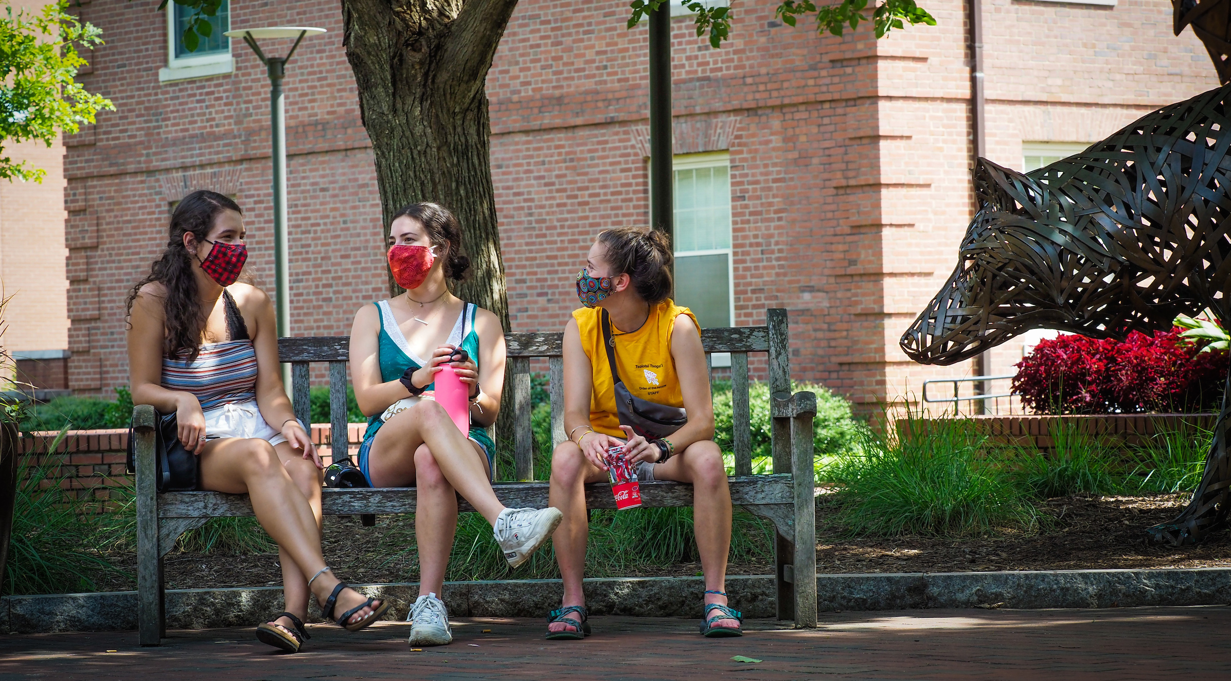 Three incoming freshman, wearing their masks, chat together in Wolf Plaza during COVID-19 move in 2020. Photo by Marc Hall