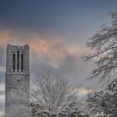 Tree branches covered in snow frames the NC State belltower after a winter storm dropped two inches in Raleigh. Photo by Marc Hall