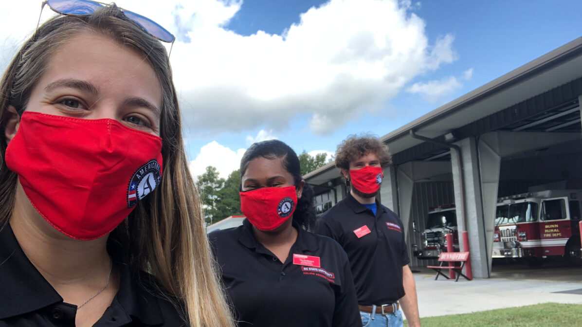 Three college advisers in NC State polo shirts pictured in front of a school building