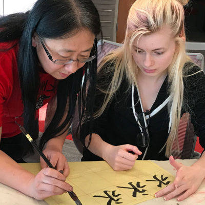 Women demonstrating Chinese calligraphy to student