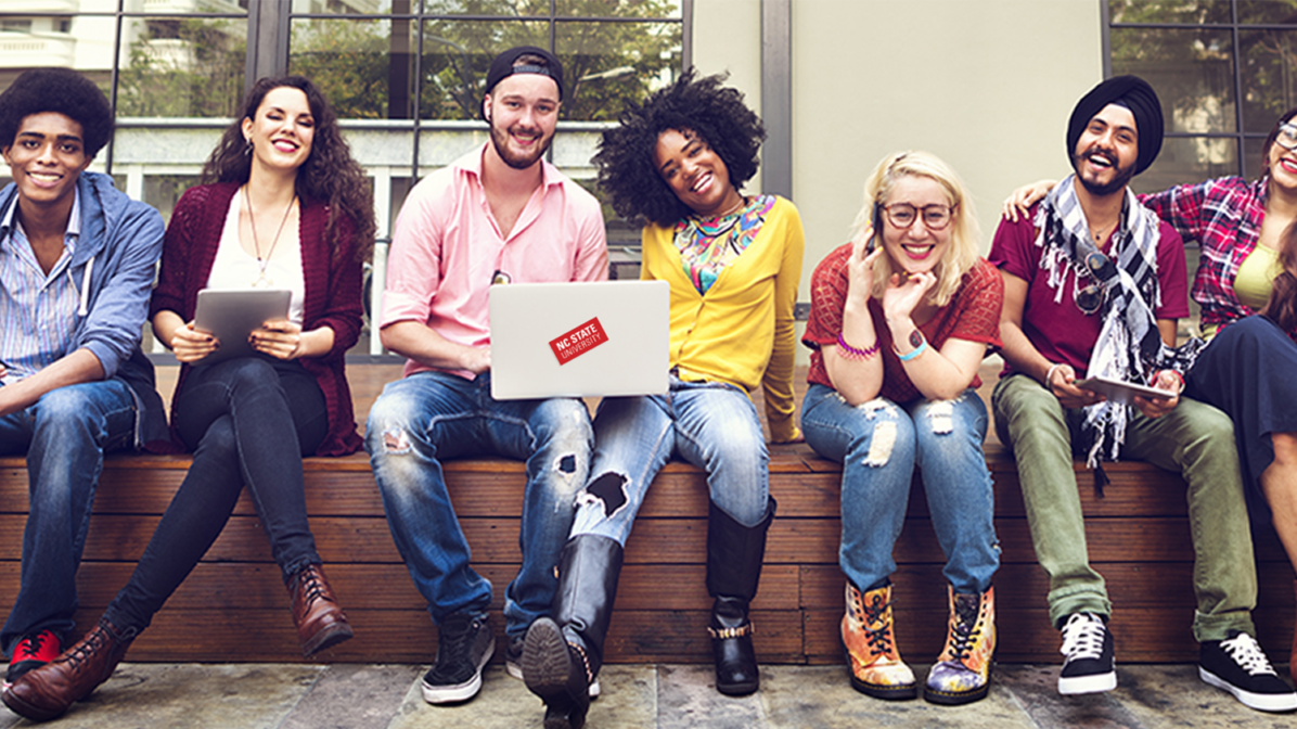Diverse students sitting on a bench and smiling